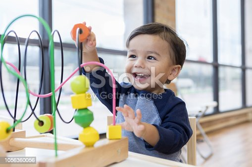 An adorable toddler boy sits at a table in a doctor's waiting room and reaches up cheerfully to play with a toy bead maze.