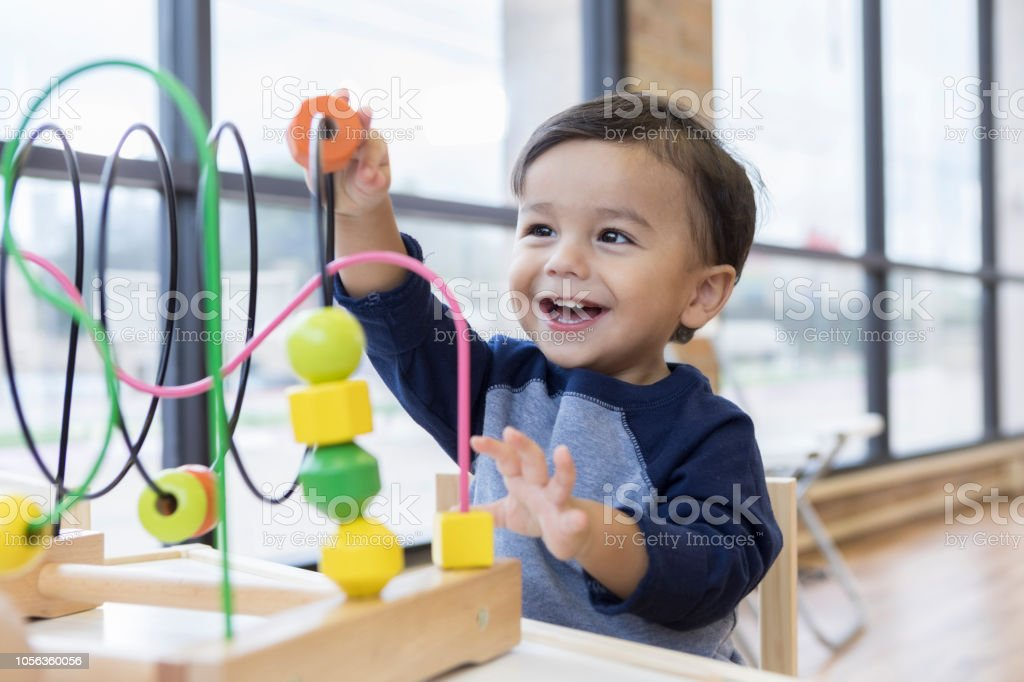 Toddler boy enjoys playing with toys in waiting room stock photo