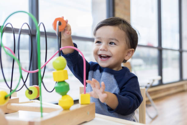 Toddler boy enjoys playing with toys in waiting room An adorable toddler boy sits at a table in a doctor's waiting room and reaches up cheerfully to play with a toy bead maze. preschool age stock pictures, royalty-free photos & images