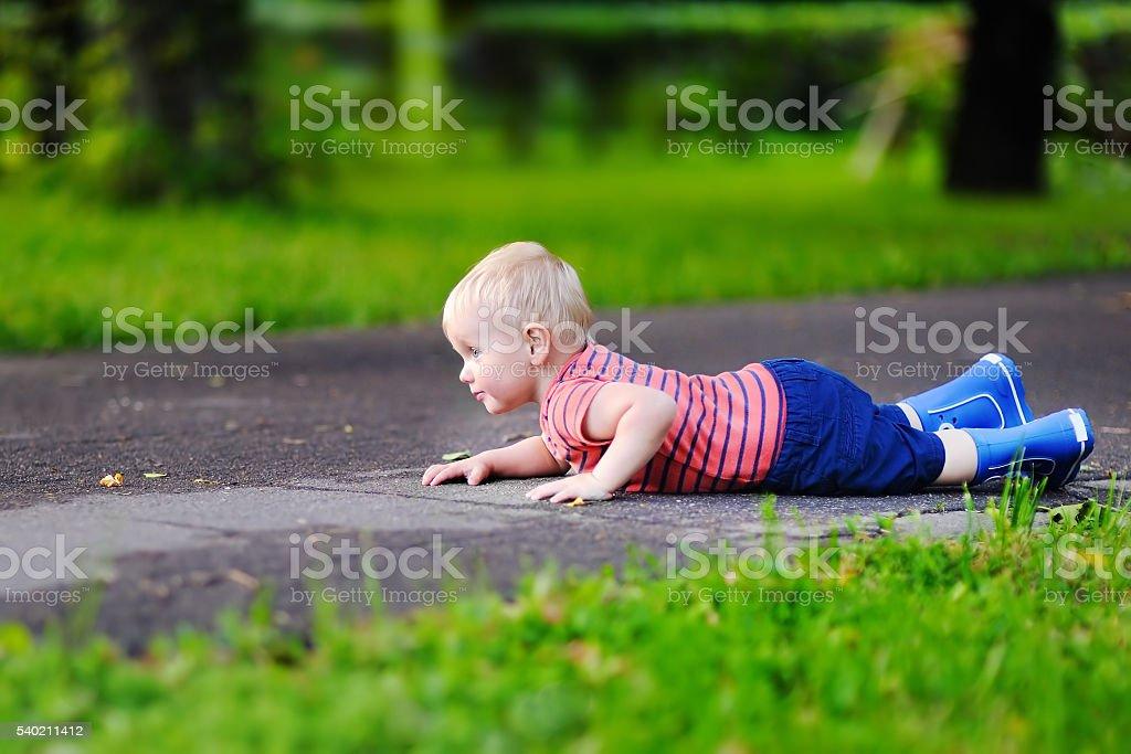 Toddler boy fell on park road stock photo