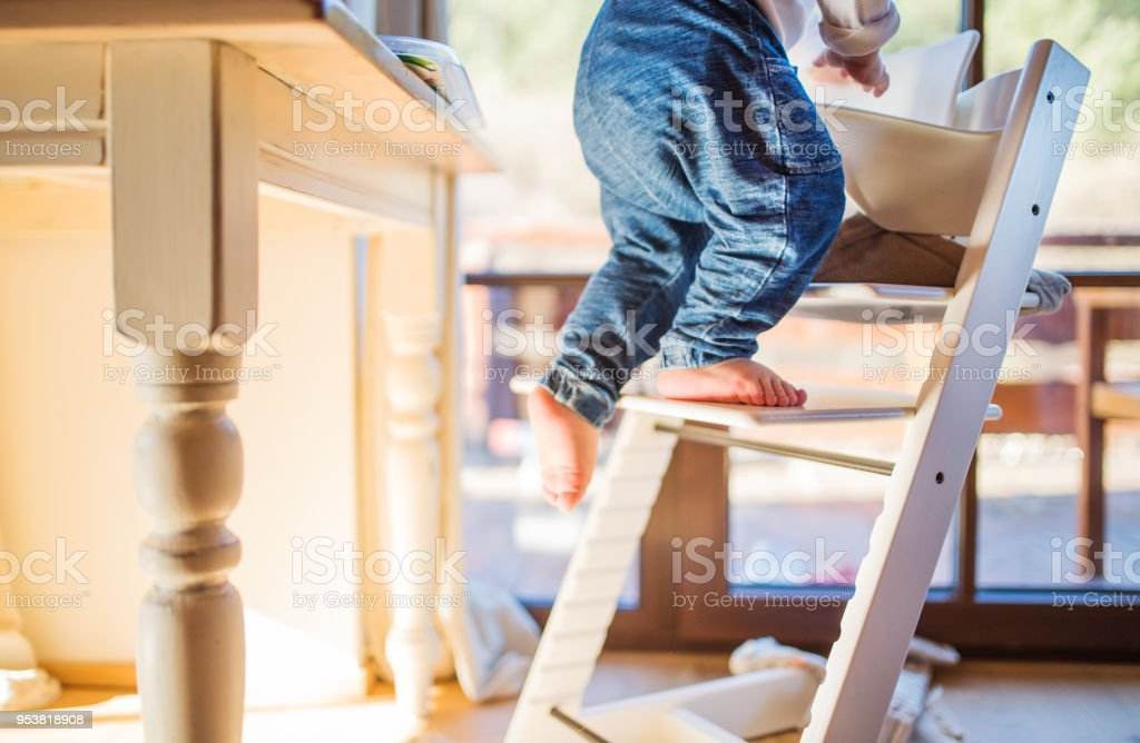 Toddler boy in a dangerous at home, climbing into highchair. stock photo