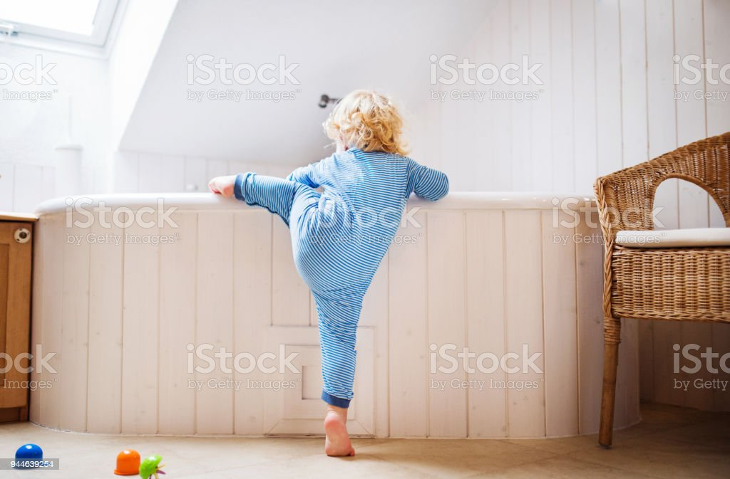 Toddler boy in a dangerous situation in the bathroom. stock photo