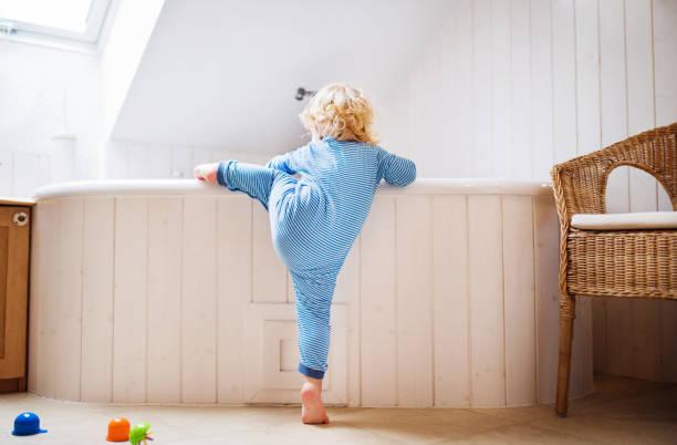 kleinkind jungen in eine gefährliche situation im badezimmer. - kinderbadewanne stock-fotos und bilder
