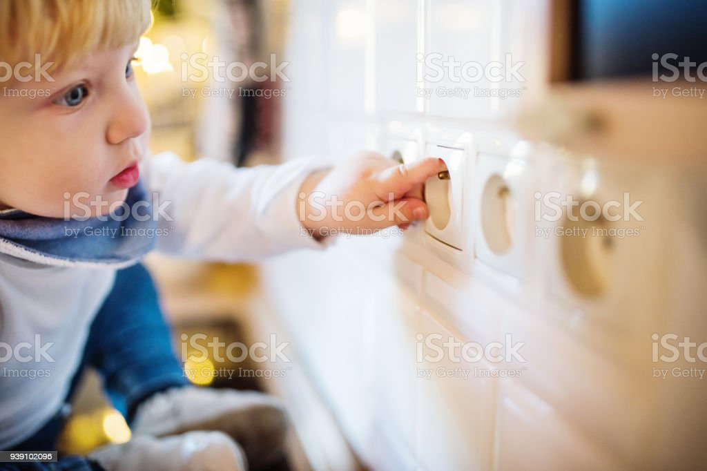 Toddler boy in dangerous situation at home. Child safety concept. stock photo