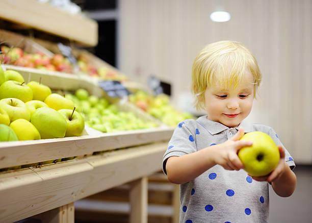 Toddler boy in food store or supermarket choosing fresh apples stock photo