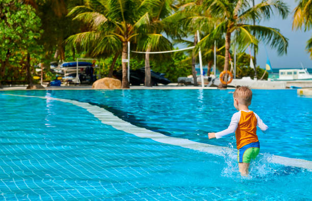 Toddler boy in resort swimming pool Three year old toddler boy in resort swimming pool. Summer family vacation at Maldives. shallow stock pictures, royalty-free photos & images