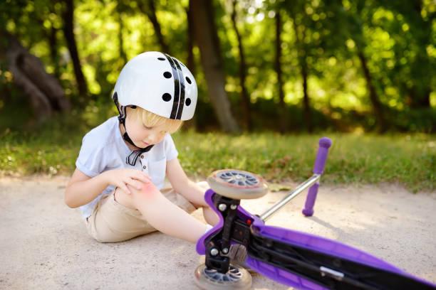 Garçon enfant en bas âge dans un casque de sécurité apprennent à conduire scooter - Photo