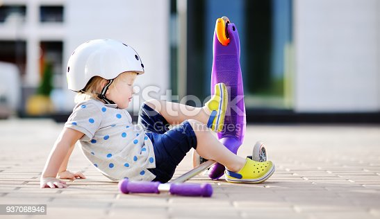 istock Toddler boy in safety helmet  learning to ride scooter 937068946