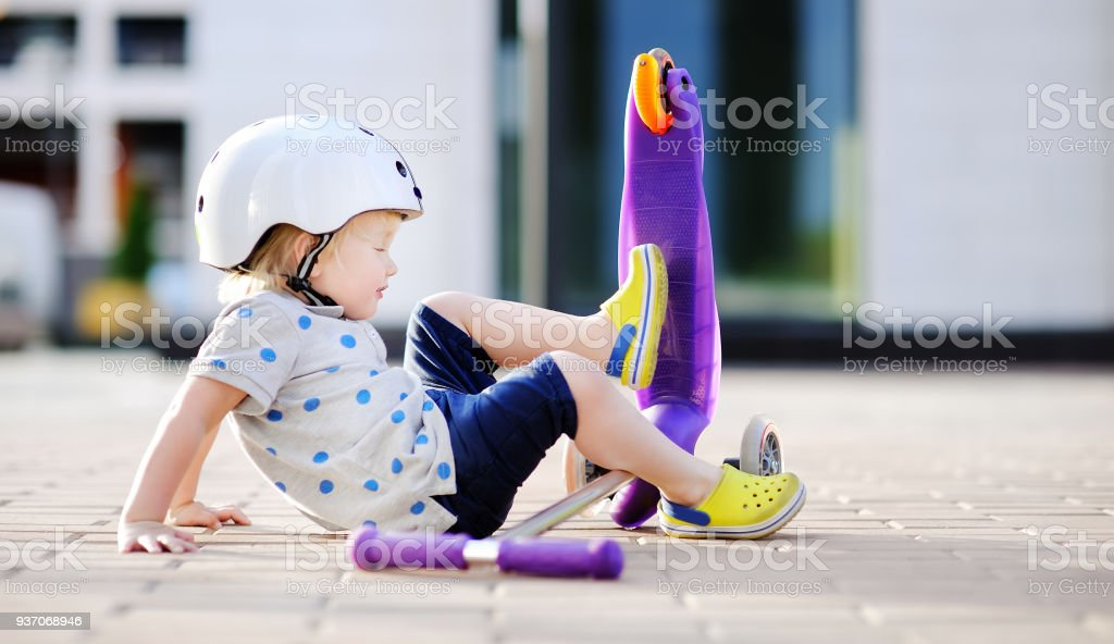 Toddler boy in safety helmet  learning to ride scooter stock photo