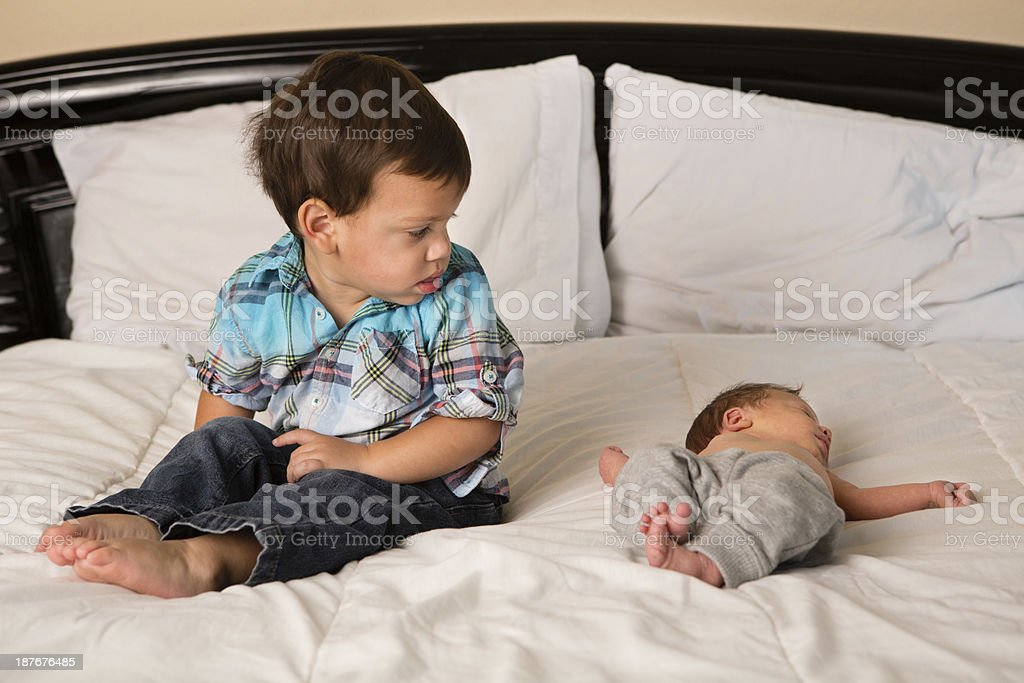 Toddler Boy Not Sure About His Newborn Brother royalty-free stock photo