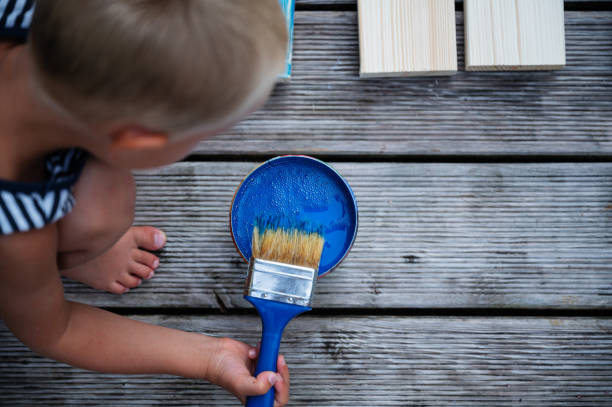 Toddler boy painting wooden planks stock photo