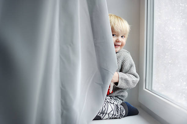 Toddler boy playing at home Toddler boy playing on the window sill at home hide and seek stock pictures, royalty-free photos & images