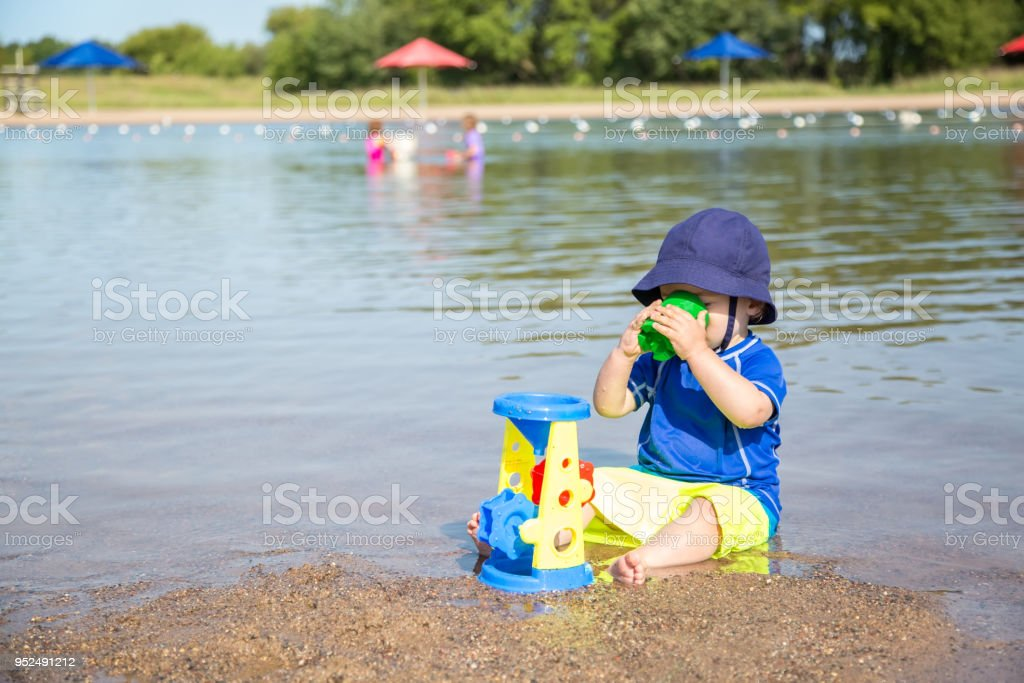 Toddler Boy Playing in Sand at Beach stock photo