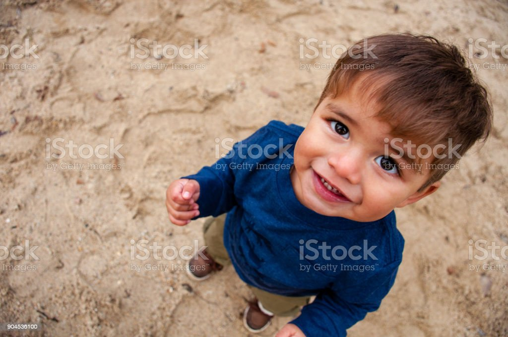 Toddler boy playing in sand stock photo