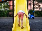 Toddler Boy Sliding in the Playground