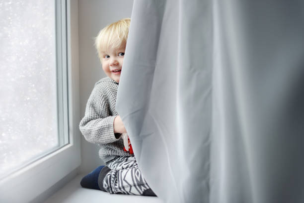 Toddler boy playing on the window sill at home Toddler boy playing on the window sill at home hide and seek stock pictures, royalty-free photos & images
