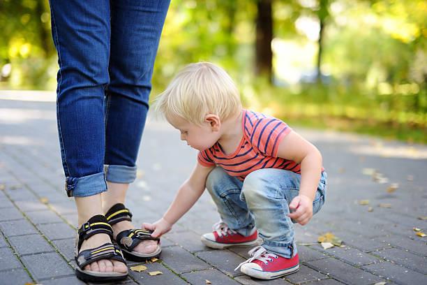 kleinkind jungen spielen mit schuhen - granny legs stock-fotos und bilder