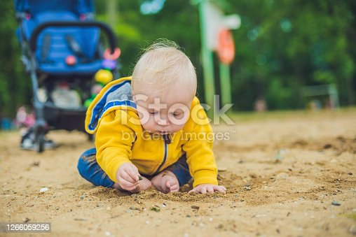 Toddler boy playing with sand on the beach development of fine motor skills.