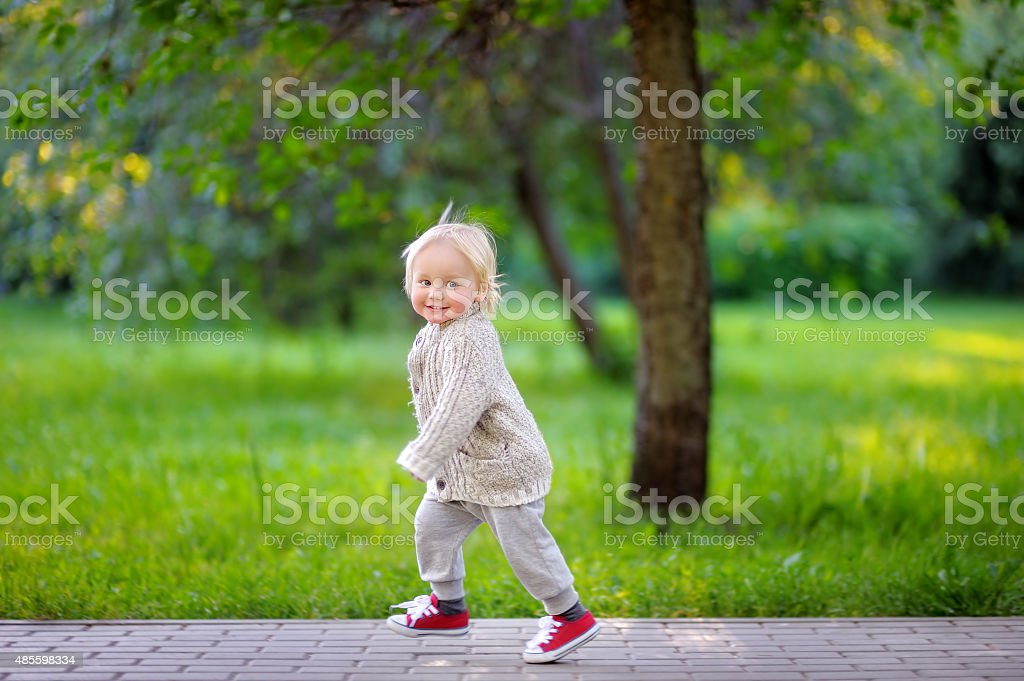 Toddler boy running in the park stock photo
