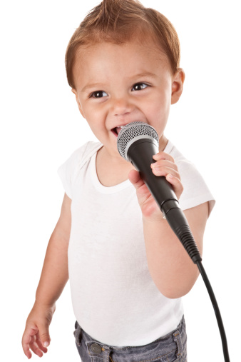 An adorable 2 year old boy smiling and singing into a microphone.