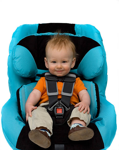 A toddler boy sitting in a blue car seat stock photo