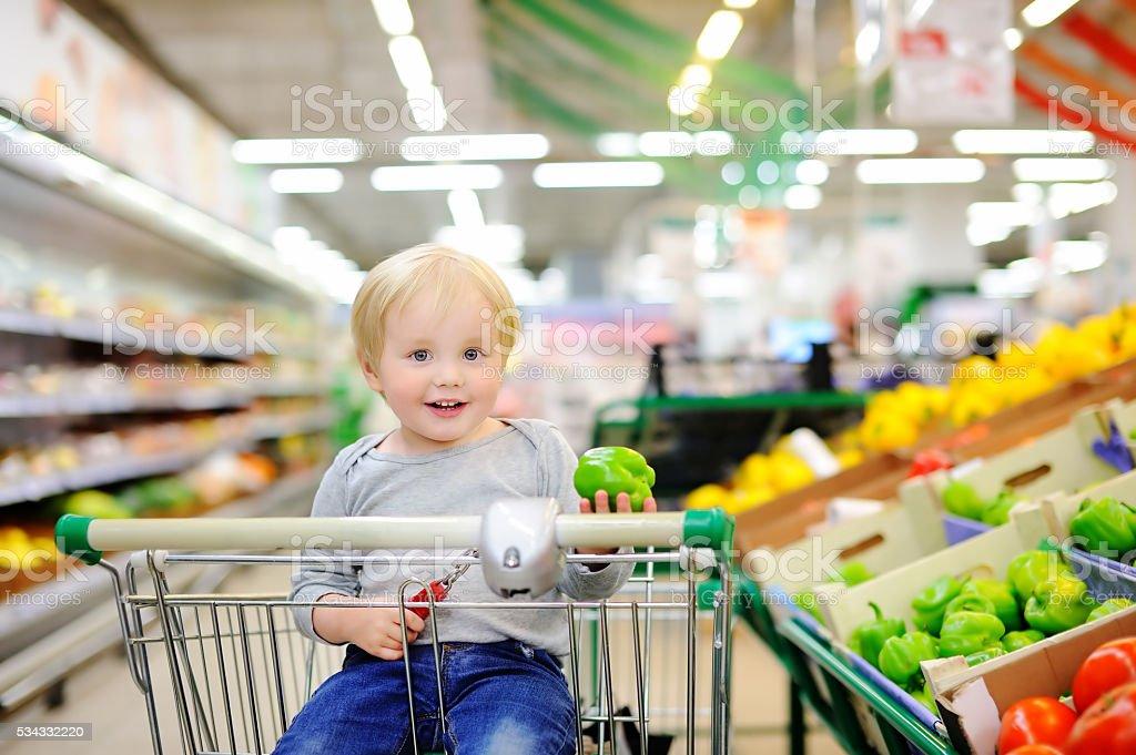 Piccolo ragazzo seduto nel carrello della spesa del supermercato - foto stock