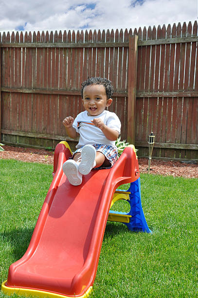 Toddler Boy Smiling Sitting on Red Slide Green Lush Grass Toddler Boy Smiling Sitting on Red Slide on Green Lush Grass haitian ethnicity stock pictures, royalty-free photos & images