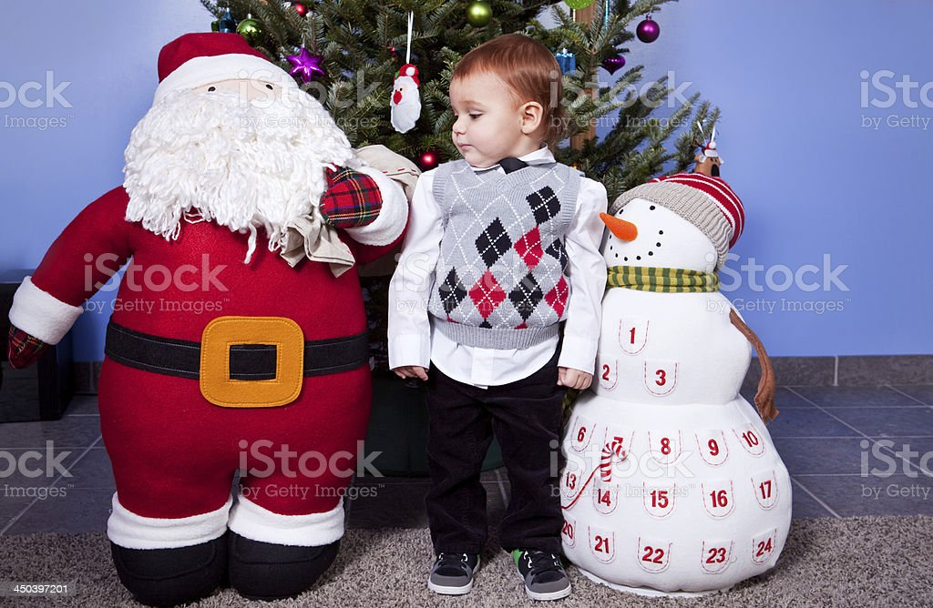 Toddler Boy Standing Between Large Christmas Decorations stock photo