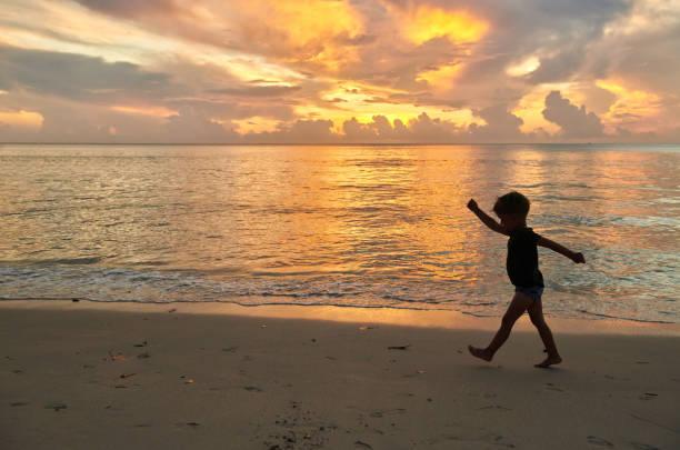 Kleinkind Junge zu Fuß am Strand bei Sonnenuntergang – Foto