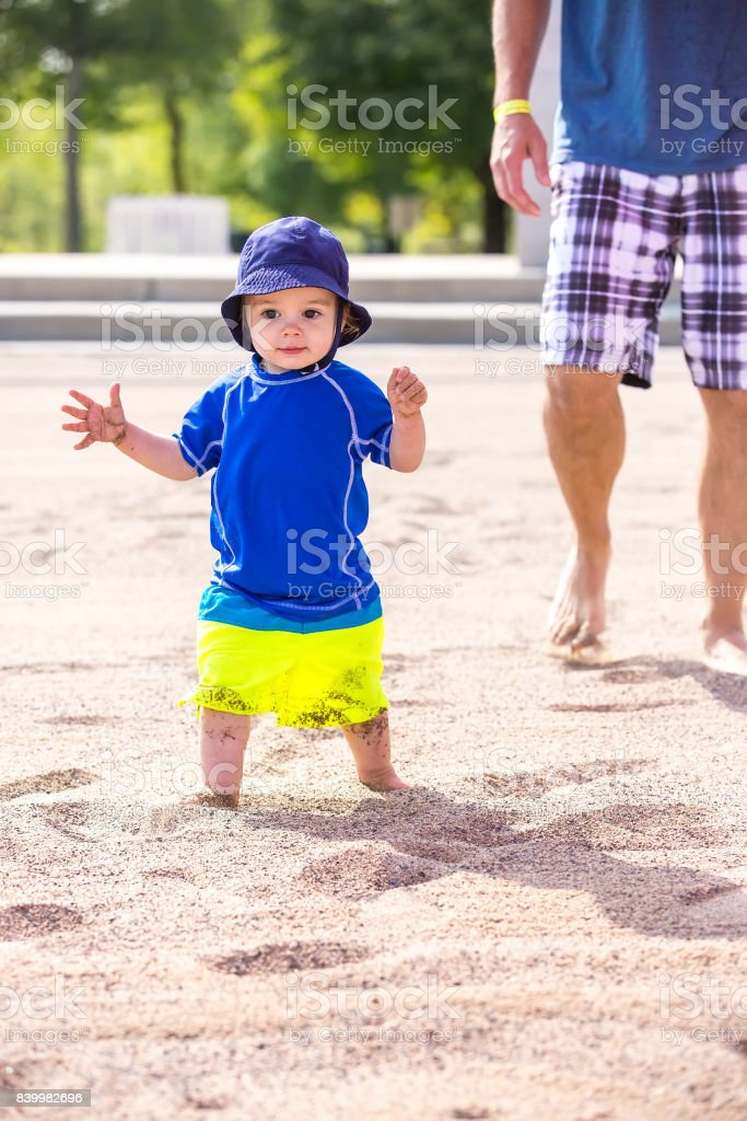 Toddler Boy Walking on Beach Followed by Dad stock photo