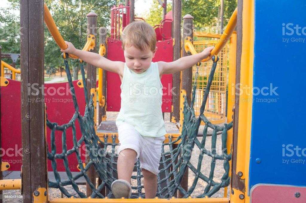 Kleinkind jungen gehen auf blauen Netzbrücke – Foto