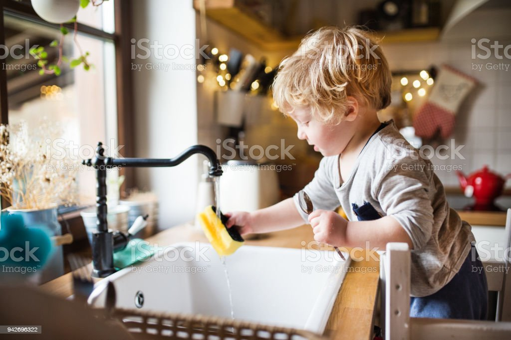 A toddler boy washing up the dishes. stock photo