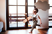 A toddler boy with carton plane and clouds playing indoors at home, flying concept.