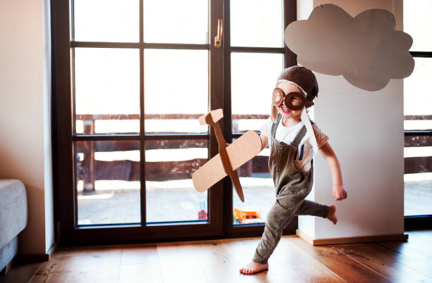 A toddler boy with carton plane playing indoors at home, flying concept. stock photo
