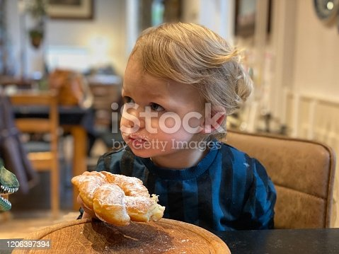 Toddler boy eating his donuts