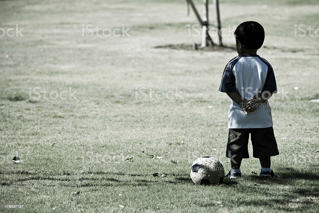 Toddler child and soccer ball standing with arms crossed royalty-free stock photo