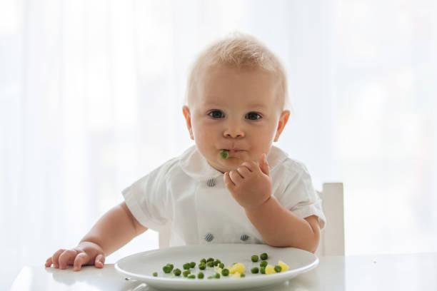 Niño niño, lindo chico en camisa blanca, comer guisantes en casa - foto de stock