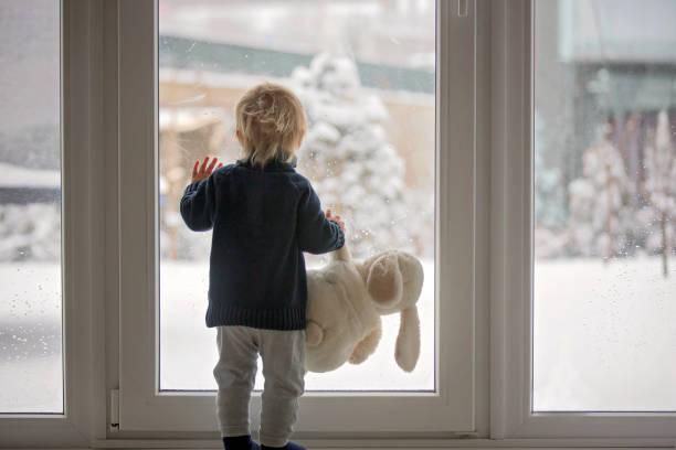 kleinkind steht vor einer großen französischen tür, lehnt sich dagegen und schaut nach draußen auf eine schneebedeckte natur - kalte sonne stock-fotos und bilder