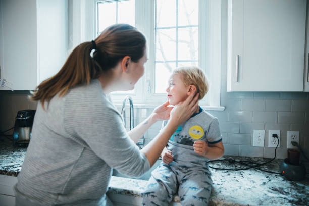 Toddler complaining ear pain to her mother stock photo