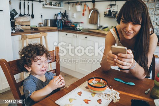 Toddler crying after making mess with his food while mother use smart phone