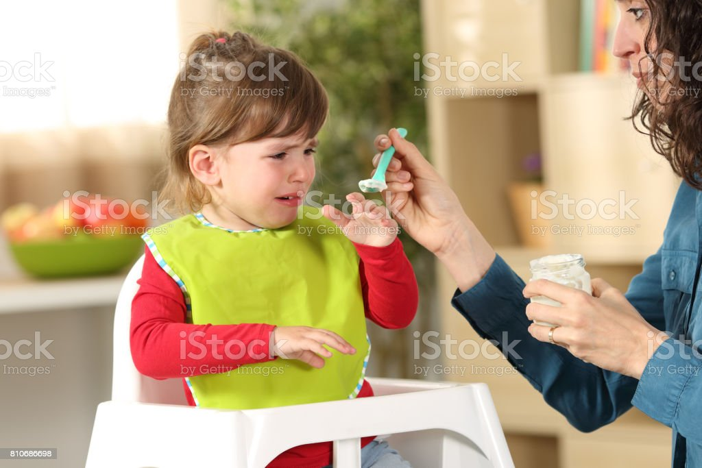 Toddler crying at lunch time stock photo