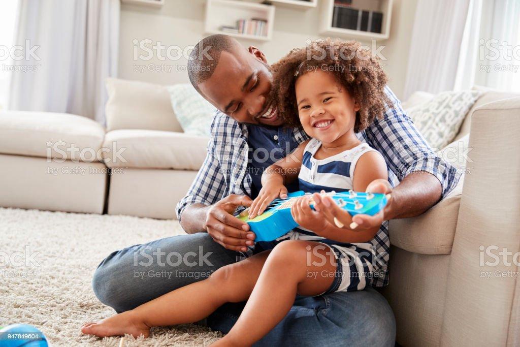 Kleinkind Tochter sitzt auf DadÕs Knie spielt Ukulele zu Hause – Foto