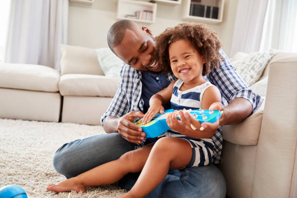 Toddler daughter sits on dadÕs knee playing ukulele at home stock photo