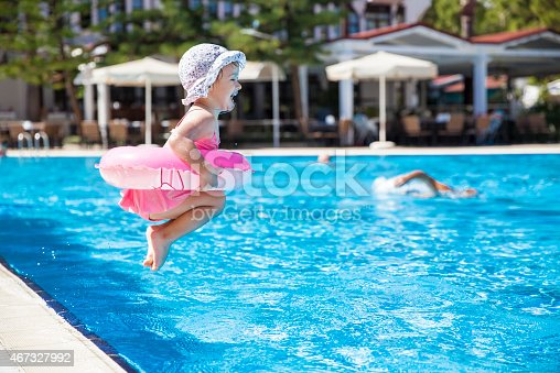 467327992istockphoto Toddler dressed in pink and jumping into a swimming pool 467327992
