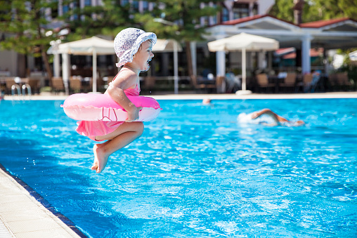 istock Toddler dressed in pink and jumping into a swimming pool 467327992
