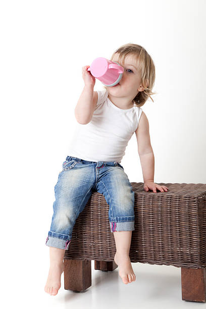 Toddler drinking from a baby cup stock photo