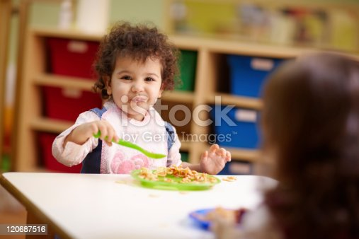 istock Toddler eating plate of food in daycare 120687516