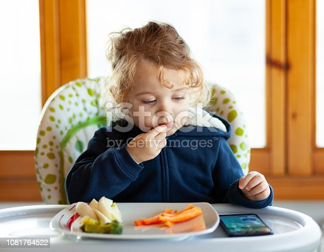 176993221istockphoto Toddler eats while watching movies on the mobile phone. 1081764522