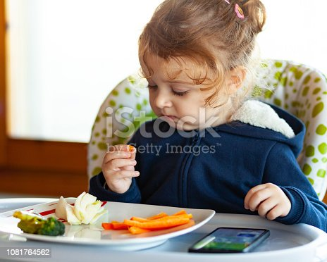 176993221istockphoto Toddler eats while watching movies on the mobile phone. 1081764562