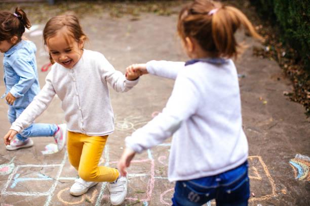 kleinkind-freunde spielen im freien himmel und hölle - himmel und hölle spiel stock-fotos und bilder